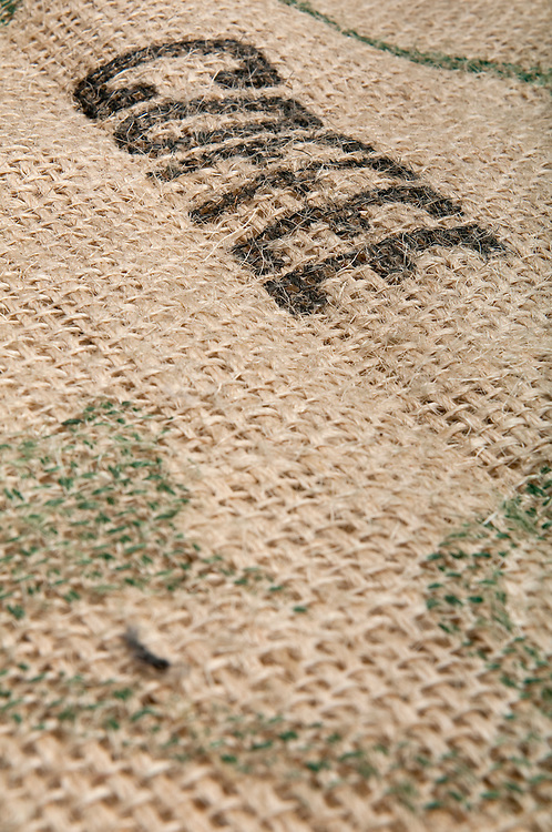 Burlap with coffee inscription for use as background or texture.  Space for copy and use of selective focus.