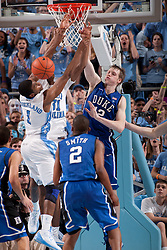 CHAPEL HILL, NC - MARCH 05: Kyle Singler #12 of the Duke Blue Devils blocks the shot of Dexter Strickland #1 of the North Carolina Tar Heels on March 05, 2011 at the Dean E. Smith Center in Chapel Hill, North Carolina. North Carolina won 67-81. (Photo by Peyton Williams/UNC/Getty Images) *** Local Caption *** Kyle Singler;Dexter Strickland