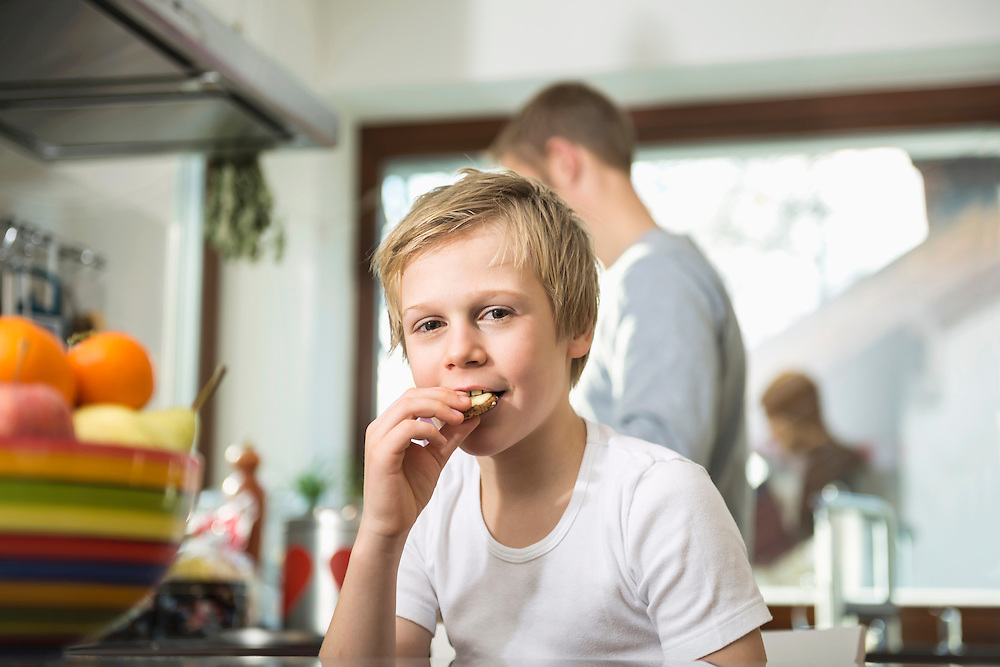 Portrait of boy eating a cookie in the kitchen