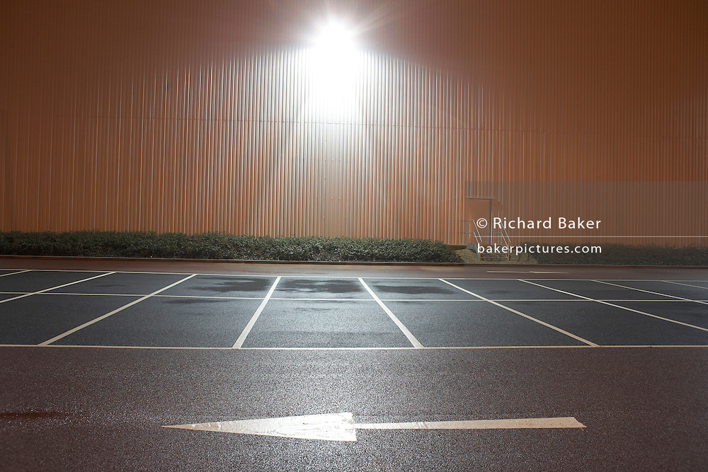 In front of empty parking bay markings, a stencilled arrow points from right to left in the foreground at the DIRFT warehouse logistics park in Daventry, Northamptonshire England. A bright light glows from the warehouse wall, shining  on to the car park creating an almost daylight landscape. This 365 acre site off Junction 18 of the M1 motorway is a hub for road, rail and service infrastructure, some 2.3m sq.ft. of distribution and manufacturing floorspace had been constructed by 2004 and occupiers including Tesco?s, Tibbett & Britten plc, Ingram Micro, Royal Mail, the W.H. Malcolm Group, Eddie Stobart Ltd, Wincanton and Exel, have been attracted to this logistics location.
