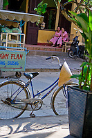 Two young Vietnamese woman sitting on a street with a bicycle and vendors cart in Hoi An's old town.