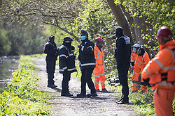 Denham, UK. 6th April, 2021. HS2 security guards, enforcement agents and tree surgeons stand alongside the Grand Union Canal during tree felling for electricity pylon relocation works in Denham Country Park connected to the HS2 high-speed rail link. Thousands of trees have already been felled in the Colne Valley where HS2 works will include the construction of a Colne Valley Viaduct across lakes and waterways and electricity pylon relocation.