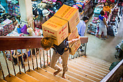 "12 APRIL 2012 - HO CHI MINH CITY, VIETNAM:   A porter makes a delivery in Binh Tay Market. The market is warren of narrow halls and alleys and steep staircases and still relies on manual labor to move goods. Binh Tay market is the largest market in Ho Chi Minh City and is the central market of Cholon. Cholon is the Chinese-influenced section of Ho Chi Minh City (former Saigon). It is the largest ""Chinatown"" in Vietnam. Cholon consists of the western half of District 5 as well as several adjoining neighborhoods in District 6. The Vietnamese name Cholon literally means ""big"" (lon) ""market"" (cho). Incorporated in 1879 as a city 11 km from central Saigon. By the 1930s, it had expanded to the city limit of Saigon. On April 27, 1931, French colonial authorities merged the two cities to form Saigon-Cholon. In 1956, ""Cholon"" was dropped from the name and the city became known as Saigon. During the Vietnam War (called the American War by the Vietnamese), soldiers and deserters from the United States Army maintained a thriving black market in Cholon, trading in various American and especially U.S Army-issue items.        PHOTO BY JACK KURTZ"