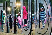 Henham Park, Suffolk, 19 July 2019. The rain arrives but children still play on the latitude sign. . The 2019 Latitude Festival.