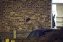 © Licensed to London News Pictures . 28/11/2013 . Manchester , UK . A man in army fatigues leaves the house with bags . Scene at 17 Mellor Street in Eccles , Greater Manchester this evening (Thursday 28th November 2013) where police have cordoned off adjoining streets and evacuated houses following the discovery of a suspicious device .  Photo credit : Joel Goodman/LNP