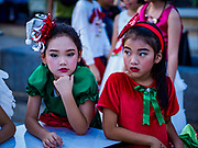 "23 DECEMBER 2018 - CHANTABURI, THAILAND: Girls performing in the pageant waits to go on stage at the Cathedral of the Immaculate Conception's Christmas Fair in Chantaburi. Cathedral of the Immaculate Conception is holding its annual Christmas festival, this year called ""Sweet Christmas @ Chantaburi 2018"". The Cathedral is the largest Catholic church in Thailand and was founded more than 300 years ago by Vietnamese Catholics who settled in Thailand, then Siam.   PHOTO BY JACK KURTZ"