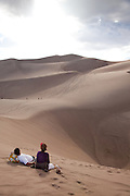 A couple rests on the edge of a sand depression that has naturally formed in the dune field of Great Sand Dunes National Park, Colorado.