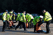 Surrey Police officers remove an Insulate Britain climate activist l who had been glued onto the clockwise carriageway of the M25 between Junctions 9 and 10 as part of a campaign intended to push the UK government to make significant legislative change to start lowering emissions on 21st September 2021 in Ockham, United Kingdom. Both carriageways were briefly blocked before being cleared by Surrey Police. The activists are demanding that the government immediately promises both to fully fund and ensure the insulation of all social housing in Britain by 2025 and to produce within four months a legally binding national plan to fully fund and ensure the full low-energy and low-carbon whole-house retrofit, with no externalised costs, of all homes in Britain by 2030.