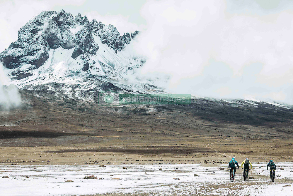 """Nov 3, 2016 - Kilimanjaro, Tanzania - Swiss-American HANS REY, German GERHARD CZERNER and Scotsman DANNY MACASKILL ride down from Kilimanjaro, towards Mawenzi. Professional mountain bike riders Hans Rey, Danny MacAskill and Gerhard Czerner are the first to take on Africa's two highest mountains back to back on mountain bikes. On Oct 26th Rey and Czerner summit Africa's second tallest mountain, Mount Kenya's Point Lenana (4,985m/16,355ft) with their mountain bikes. On November 3rd, only one week later, together with urban trials YouTube sensation Danny MacAskill; they also summited Mount Kilimanjaro (5,895m/19,340ft), the Roof of Africa. There have only been a handful of people who have taken their bikes to either Mount Kilimanjaro or Mount Kenya in the past, but none have achieved both, one straight after the other. Others carried their bikes for the majority both up and down the mountains, while Rey (Swiss/American), MacAskill (Scottish) and Czerner (German) rode 98% of the descent. They are world renown extreme bikers and their feats will be featured in a TV documentary, magazine stories and an upcoming film about the Mountain Bike Freeride history, titled """"Nothin For Free"""" produced by Freeride Entertainment. The hardest part about the trip was adjusting to the high altitude. The terrain is extremely technical and challenging, several different eco-systems are being crossed on the way, from rainforests to glaciers. It took the riders 4 days to summit and traverse Mount Kenya, and 6 days to summit and descend Mount Kilimanjaro. The National Parks plan on extending their programs to permit bike riders in the future. For those that dare, there are adventures and ultimate challenges both physically and mentally awaiting them. (Credit Image: © Martin Bissig via ZUMA Wire)"""