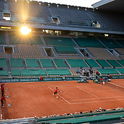 PARIS, FRANCE June 5.  The sun goes down over Paris as Roger Federer of Switzerland and Dominik Koepfer of Germany compete in the evening match in the empty stadium of Court Philippe-Chatrier during the third round of the singles competition at the 2021 French Open Tennis Tournament at Roland Garros on June 5th 2021 in Paris, France. (Photo by Tim Clayton/Corbis via Getty Images)