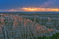 A distant lightning storm moves south past the Badlands in South Dakota. The red sky in the west was casting a soft glow on the tops of the cliffs. This was a typical late summer evening when a thunderstorm formed over the Black Hills and moved out across the plains.<br />