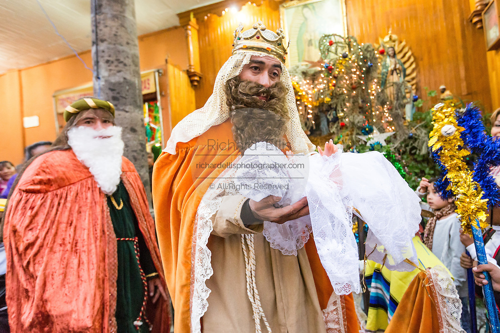 The Three Kings pick up the baby Jesus doll from a nativity crche during El Dia de Reyes January 6, 2016 in San Miguel de Allende, Mexico. The traditional festival marks the culmination of the twelve days of Christmas and commemorates the three wise men who traveled from afar, bearing gifts for the infant baby Jesus.