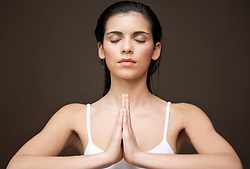 Close up of a woman with her hands in the prayer position