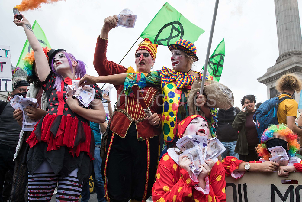 A troupe of clowns holding banknotes joins fellow climate activists from Extinction Rebellion at a 'Carnival of Corruption' protest against the government's facilitation and funding of the fossil fuel industry on 3 September 2020 in London, United Kingdom. Extinction Rebellion activists are attending a series of September Rebellion protests around the UK to call on politicians to back the Climate and Ecological Emergency Bill CEE Bill which requires, among other measures, a serious plan to deal with the UK's share of emissions and to halt critical rises in global temperatures and for ordinary people to be involved in future environmental planning by means of a Citizens' Assembly.
