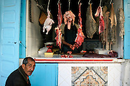 Morocco, Essaouira. Man sitting at the butcher's shop.