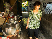 08 APRIL 2016 - BANGKOK, THAILAND:   A woman walks through the kitchen on the sidewalk in front of her home in Mahakan Fort. Kitchens in Thai slum communities are frequently on the sidewalk in front of the home. The community is known for fireworks, fighting cocks and bird cages. Mahakan Fort was built in 1783 during the reign of Siamese King Rama I. It was one of 14 fortresses designed to protect Bangkok from foreign invaders, and only of two remaining, the others have been torn down. A community developed in the fort when people started building houses and moving into it during the reign of King Rama V (1868-1910). The land was expropriated by Bangkok city government in 1992, but the people living in the fort refused to move. In 2004 courts ruled against the residents and said the city could take the land. The final eviction notices were posted last week and the residents given until April 30 to move out. After that their homes, some of which are nearly 200 years old, will be destroyed.   PHOTO BY JACK KURTZ
