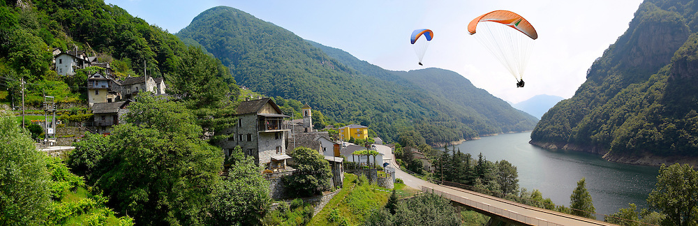 Para gliders over the rustic alpine village of Vogorno with paragliders over lake Vogorno, Val Verzasca, Tocino Switzerland .<br /> <br /> Visit our SWITZERLAND  & ALPS PHOTO COLLECTIONS for more  photos  to browse of  download or buy as prints https://funkystock.photoshelter.com/gallery-collection/Pictures-Images-of-Switzerland-Photos-of-Swiss-Alps-Landmark-Sites/C0000DPgRJMSrQ3U