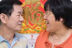 Couple standing in front of Chinese calendar showing symbol of good luck and prosperity,