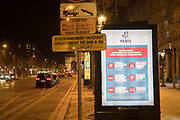 """March, 19th, 2020 - Paris, Ile-de-France, France: Public notice warning about Coronavirus on the empty Avenue des Champs Elysees in Paris, on the third day of a near total lockdown imposed in France. All journeys outside the home unless justified for essential professional or health reasons are outlawed. Anyone flouting the new regulations is punished with monetary fines. French police control of citizens and inspection of valid papers allowing citizens to travel. The most extreme measures so far in France to control the spread of the Coronavirus. Earlier in the week, President of France, Emmanuel Macron, said that citizens must stay at home from midday on Tuesday for at least 15 days. He said """"We are at war, a public health war, certainly but we are at war, against an invisible and elusive enemy"""". Nigel Dickinson"""