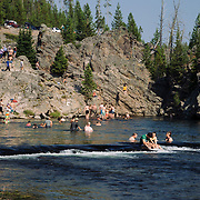 One girl jumps a cliff as many others swim in the Firehole River near Old Faithful.