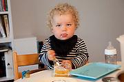 Ottersland-Dahl family, of Gjettum, Norway (outside Oslo). Sverre, 1.5, with cheese for spaghetti dinner. Model-Released.
