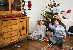 Man throwing Christmas gifts at home