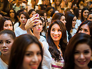 "25 MARCH 2015 - BANGKOK, THAILAND: A contestant uses her smart phone to take a ""selfie"" before she goes on stage during the first round of the Miss Tiffany's contest at CentralWorld, a large shopping mall in Bangkok. Miss Tiffany's Universe is a beauty contest for transgender contestants; all of the contestants were born biologically male. The final round will be held on May 8 in the beach resort of Pattaya. The final round is televised of the  Miss Tiffany's Universe contest is broadcast live on Thai television with an average of 15 million viewers.     PHOTO BY JACK KURTZ"