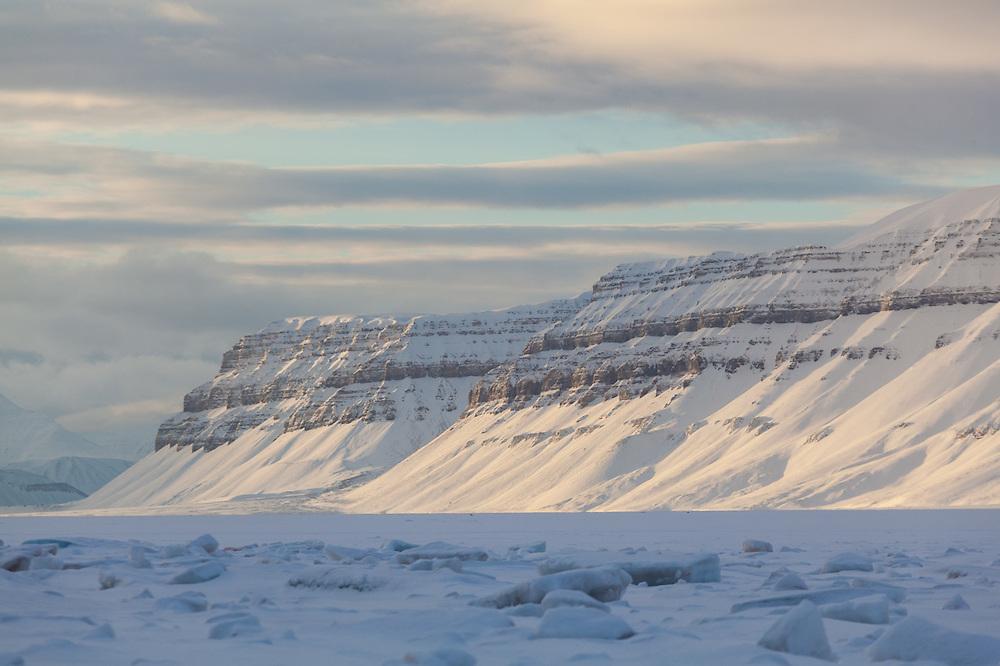 Sea ice fills Templefjorden, Svalbard. Sindballefjellet is visible across the fjord.