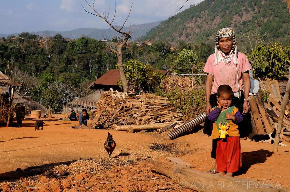 Akha woman and a child posing with a village at the background.
