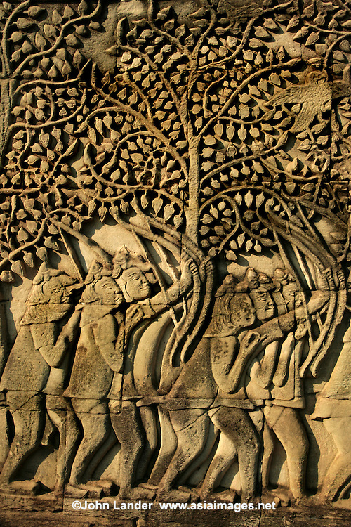 Bayon is known for its impressive sets of bas-reliefs, which present an unusual combination of mythological, historical, and even mundane scenes such as these workmen carrying a tree.