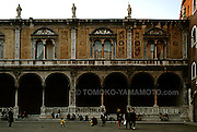 The building of the Loggia del Consiglio is the finest Renaissance building, built between 1476 and 1493, in Verona, Italy.  It is located behind the statue of Dante at the Pizza dei Signori. In front of this arcaded building with yellow and red frescoes on the upper floor and statues on the rooftop, people are enjoying their late afternoon passagiata.  A little girl in a yellow jacket walks toward a pigeon, watched by her parents and sibling. Photo of Verona, Italy by Tomoko Yamamoto; 38MB maximal file size