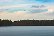 Cloudy sky, dark pine forest and frozen surface of lake Purezers in winter, near Puikule, Latvia Ⓒ Davis Ulands   davisulands.com