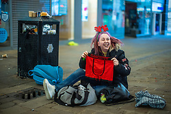 © Licensed to London News Pictures. 25/12/2020. Manchester, UK. Homeless couple Nathan Dale (25) and AMY DEWHURST (26) (pictured opening a present handed to the couple as a gift) , on Market Street in Manchester City Centre on Christmas Day . Photo credit: Joel Goodman/LNP