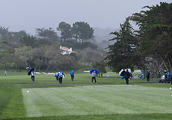 February 10, 2019 - Pebble Beach, CA, U.S. - PEBBLE BEACH, CA - FEBRUARY 10: Players from group 2 make their way down the fairway of hole 1 in a downpour of hail during the final round of play at the AT&T Pebble Beach Pro-Am on Sunday, February 10, 2019 in Pebble Beach, CA. (Photo by Douglas Stringer/Icon Sportswire) (Credit Image: © Douglas Stringer/Icon SMI via ZUMA Press)