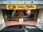18 AUGUST 2015 - BANGKOK, THAILAND: A worker at the Erawan Mall sweeps up broken glass from shattered windows in front of the mall's food court. An explosion at Erawan Shrine, a popular tourist attraction and important religious shrine in the heart of the Bangkok shopping district, killed at least 20 people and injured more than 120 others, including foreign tourists, during the Monday evening rush hour. Twelve of the dead were killed at the scene. Thai police said an Improvised Explosive Device (IED) was detonated at 18.55. Police said the bomb was made of more than six pounds of explosives stuffed in a pipe and wrapped with white cloth. Its destructive radius was estimated at 100 meters.    PHOTO BY JACK KURTZ