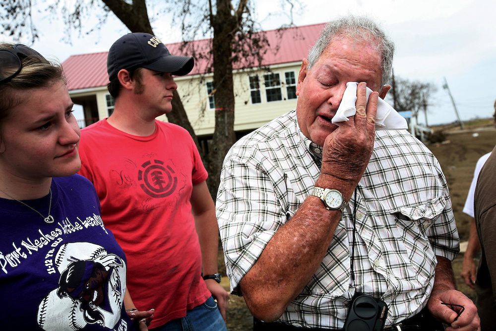 Earl Kile, right, an 82-year-old lifelong resident of Sabine Pass, Texas, breaks into tears when he sees his home for the first time after Hurricane Ike Friday September 19, 2008.  His grandson, Eric Kile, center, and Eric's fiancee Shae Caldwell helped Earl and his wife salvage what they could from the destroyed home.