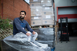 """© Licensed to London News Pictures. 07/05/2020. Salford, UK. Manager at Puro Medico SALAIMAAN MAJID (28) sits in front of remaining stock of masks stored outside the warehouse from where the PPE was stacked up when it was stolen . £166,000 (one hundred and sixty six thousand pounds) worth of protective masks , which were destined for the NHS and care homes , have been stolen from a warehouse overnight (6th-7th May 2020) in what Greater Manchester Police are describing as a """" targeted burglary """" . Thieves cut the shutters at the loading bay of Puro Medico - which specialises in importing PPE such as masks from China and hand sanitiser from Poland - and stole several pallets of stock , which was loaded on to vans over a two hour period . Photo credit: Joel Goodman/LNP"""
