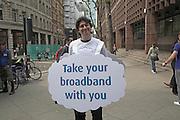 Smiling man holding sandwich board for mobile broadband, London, England