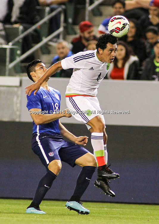 4月22日,美國隊球員Mario Rodriguez (右)與墨西哥隊球員Luis Guzmán(左)在比賽中爭球。當天晚上,在美國洛杉磯家得寶中心球場舉行的國際足球友誼賽中,美國隊對陣墨西哥隊。美國隊以3-0戰勝墨西哥隊。(新華社發 趙漢榮攝)<br /> Mexico's defender Luis Guzmán #4, right, and United States' forward Mario Rodriguez #18, left, battle for a head ball during a men's national team international friendly match, April 22, 2015, at StubHub Center in Carson, California, United State. United States won 3-0. (Xinhua/Zhao Hanrong)(Photo by Ringo Chiu/PHOTOFORMULA.com)