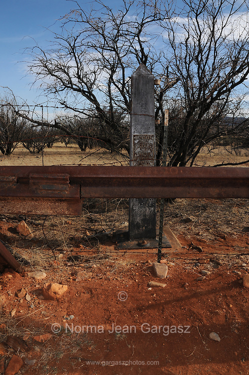 Holes have been cut in the fence at the Mexican border that divides Sonora with Lochiel, Arizona, USA, a former official port-of-entry.  A concrete post originally defined the international line.