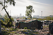 A woman removes items from the roof of her home. The Belville camp in New Belgrade on the morning of its destruction by the Belgrade city government. Many residents were moved to container homes at the edge of the city.