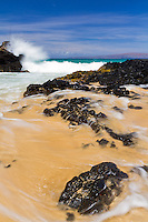 A rocky inlet and crashing waves at Makena Cove, also known as Secret Beach, in Maui, Hawaii.