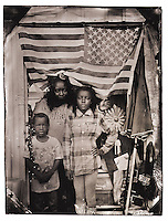 The flag hanging in the backdoor of Kennetta Sutton's, 29, booth at the Waldo Flea Market off U.S. 301 caught my eye, then I noticed<br /> her packing up items inside after a day of sales. She said she rented the booth on a whim and has been selling various wares on Saturdays for the past few years. We made<br /> one plate while her children Kayla, 10, and Richard, 7, played nearby. They were curious about the process after watching the first<br /> image appear in the fixer, so we took another. A process artifact appeared just below Kennetta's head, eroding the silver in that<br /> spot. There was no time for another with the sun fading to an impractically long exposure for children and her need to get everything packed up before complete darkness.