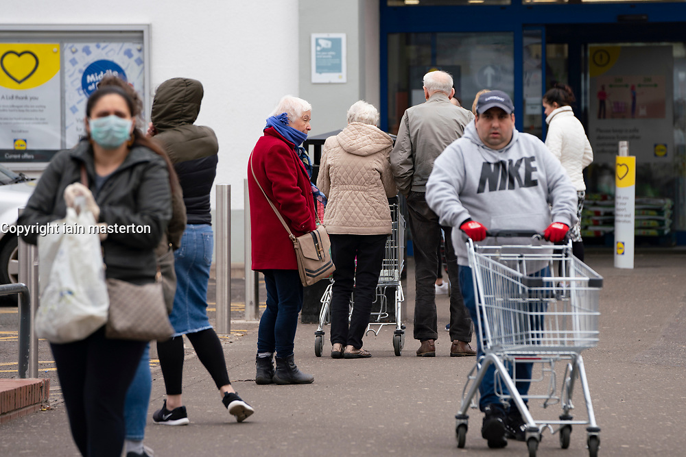 Glasgow, Scotland, UK. 3 April, 2020. Images from the south side of Glasgow at the end of the second week of Coronavirus lockdown. Long queue outside Lidl supermarket in Govanhill.  Iain Masterton/Alamy Live News