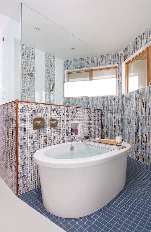 Spacious modern bathroom with unique tiling and sleek bathtub