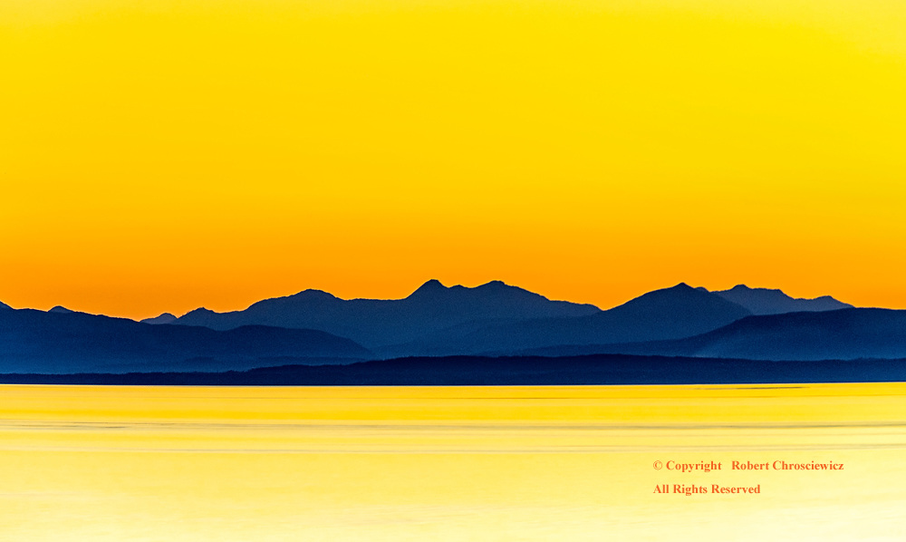Silhouette at Sunset:  Distant Vancouver Island is held in a blue silhouette under a yellow sunset, Vancouver British Columbia Canada.