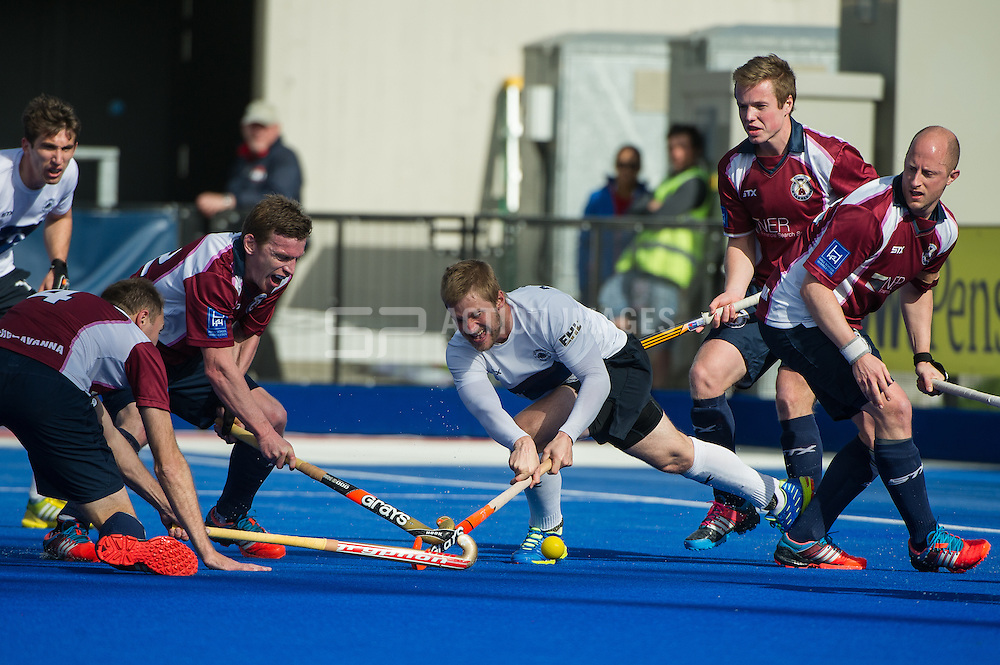 East Grinstead's Ashley Jackson tries to get a shot off while surrounded by Wimbledon players. East Grinstead v Wimbledon -  Now: Pensions Men's Hockey League Championship Final, Lee Valley Hockey & Tennis Centre, London, UK on 12 April 2015. Photo: Simon Parker