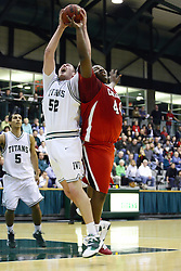 29 January 2011: Ryan Connolly and Tyer Pierce struggle for the ball during an NCAA basketball game between the Carthage Reds and the Illinois Wesleyan Titans at Shirk Center in Bloomington Illinois.