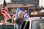 """26 SEPTEMBER 2020 - DES MOINES, IOWA: A woman in a pro Donald J. Trump motorcade gives a """"thumbs up"""" as the truck she's riding in crosses the Court Avenue Bridge. More than 1,500 people in 500 vehicles participated in motorcade through Des Moines Saturday. They started in the suburbs south of downtown, drove through downtown, and ended at the State Capitol.       PHOTO BY JACK KURTZ"""