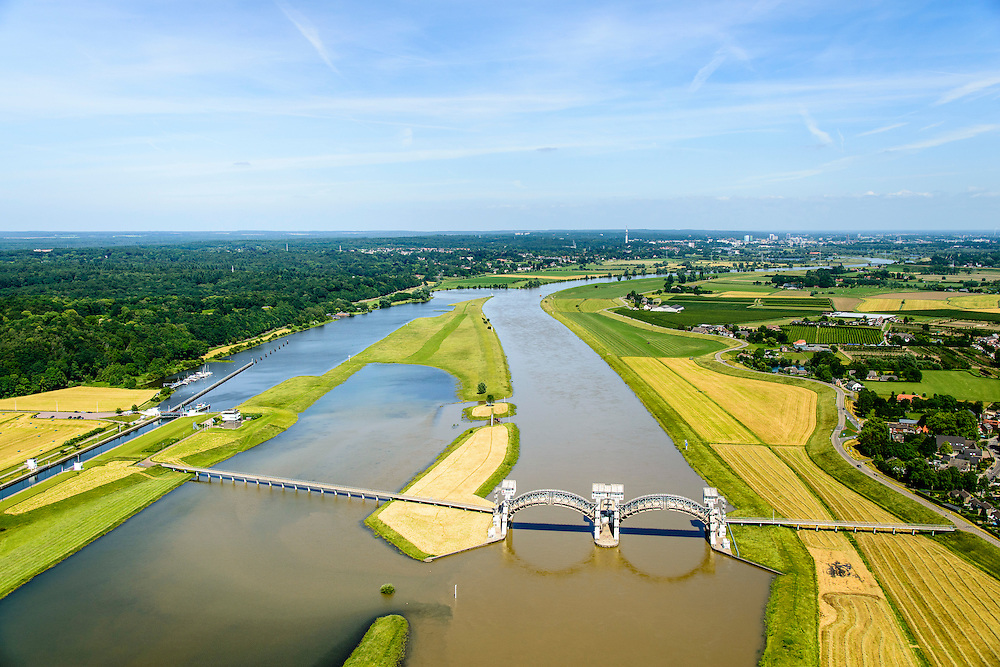 Nederland, Gelderland, Gemeente Overbetuwe, 09-06-2016; stuw bij Driel in de Neder-rijn. In verband met het hoge water ten gevolge van overvloedige regenval in Duitsland is de stuw is geopend, een uitzonderlijke situatie in deze periode van het jaar. De stuw bij Driel, de Kraan van Nederland, zorgt voor afvoer van het water van de Rijn via Nederrijn en Lek. Het stuwensemble wordt gerenoveerd en gemoderniseerd.<br /> Due to the hight water levels as a result of heavy rainfall in Germany, the weir has been opened, an exceptional situation in this time of the year.<br /> The weir at Driel, nicknamed 'main valve of the Netherlands', provides drainage of water from the Rhine via the Lower Rhine and Lek to the sea. The ensemble of locks and weir will be renovated and modernized.<br /> <br /> luchtfoto (toeslag op standard tarieven);<br /> aerial photo (additional fee required);<br /> copyright foto/photo Siebe Swart